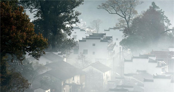 Village shrouded by morning mist in E China