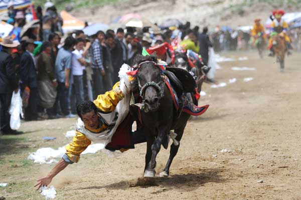 A ceremonial scarf is the target for a rider as the Ongkor Festival, a traditional Tibetan celebration to prepare for a bumper harvest, is staged in Lhasa on Thursday. PHOTO BY LI ZHOU / FOR CHINA DAILY