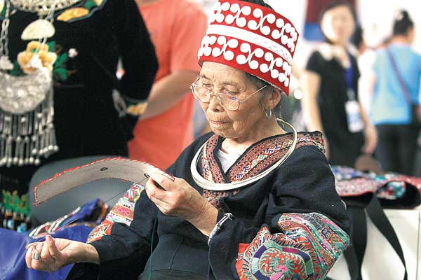 Yang Huani, 82, can hardly read or write but she sews whatever she sees around her. [Zhu Xingxin / China Daily]