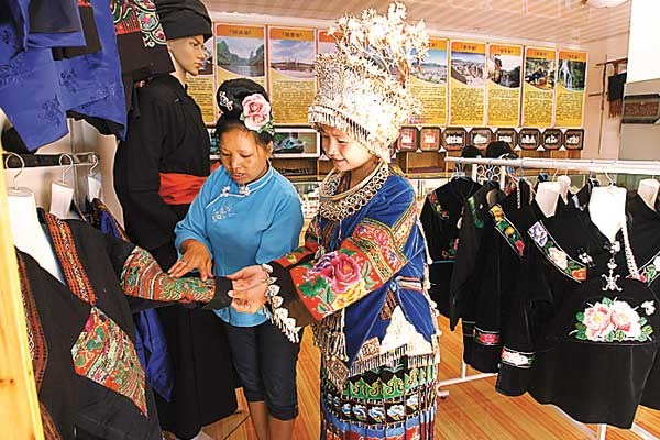 Miao woman Yu Xiaoye (right) shows off the handmade traditional costumes at a small shop in Kaili, Guizhou province.