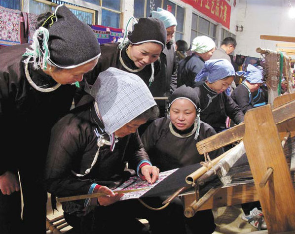 A Dong master shows her brocade technique to her peers. Yang Shaoquan / For China Daily