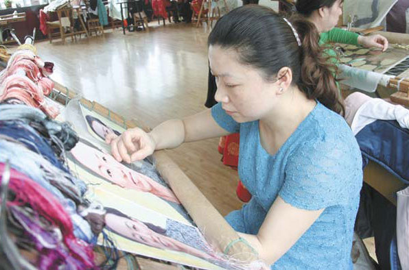 Xiangxiu embroidery master Yuan Xiaoqin works on a piece of work featuring portraits. Photos provided to China Daily