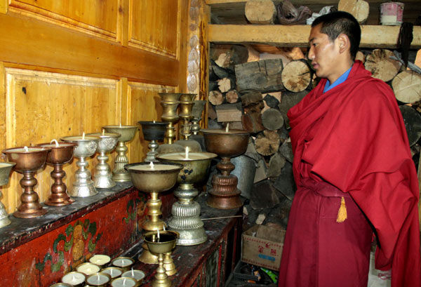 Lhasang Pasang from Ganden Sumtsenling Monastery selects a butter lamp for a visitor. hu yongqi / China Daily