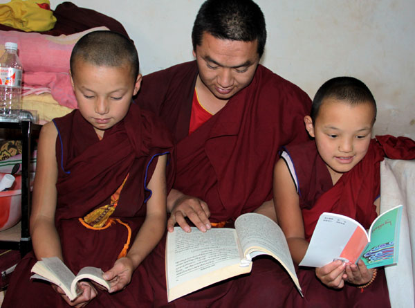 Three monks study Tibetan Buddhist scriptures in their dorm at Dondrup Ling Monastery. Hu Yongqi / China Daily