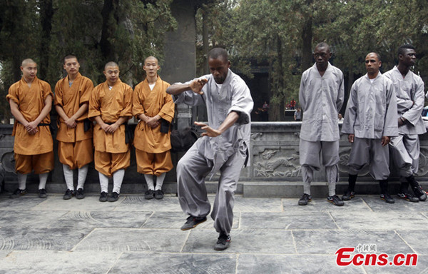 An African young man showcases Shaolin Kung Fu skills at Shaolin Temple in Zhengzhou city of Henan province on September 25, 2013. A total of 20 African young men from five African countries began their three-month Kung Fu learning tour here on Wednesday. [Photo/CFP]