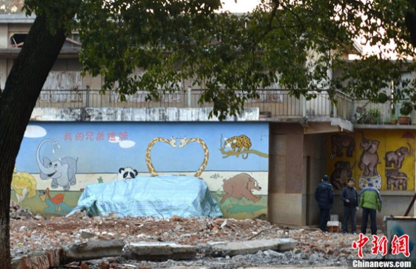Staff members of the zoo of Kunming look over the elephant enclosure on Feb 19, 2014 after a zookeeper died in it on Wednesday afternoon.