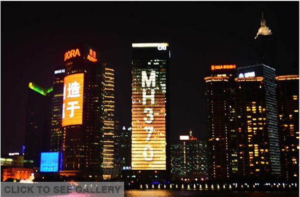 "Photo taken on March 11, 2014 shows ""MH370, We Are Waiting for You Back Home"" displayed on a skyscraper at the Lujiazui Financial District in Shanghai, east China. (Xinhua/Shen Chunchen)"