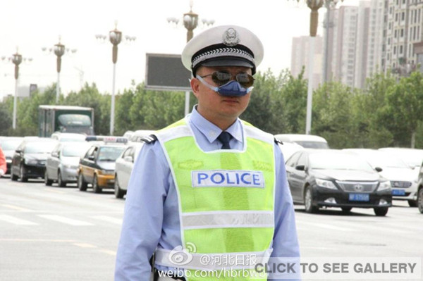 A traffic police, wearing an anti-smog nasal air filter, is on duty in Shijiazhuang of Hebei province. [Photo/ Weibo account of Hebei Daily]
