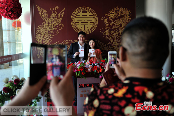 """A couple poses for photos at Chaoyang district civil affairs bureau in Beijing on May 20, 2014. May 20 has an auspicious meaning since it has a similar pronunciation to """"I love you"""" in Chinese. The day sees marriage registration boom across China every year. [Photo: Chinanews.com / Jin Shuo]"""