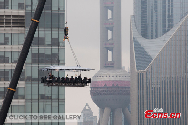 Dinner guests dine on a platform, 50 meters in the sky above Shanghai for a novelty experience costing 1,888 yuan ($303) to 8,888 yuan ($1,429) on June 27, 2014. [Photo: China News Service / Zhang Hengwei]