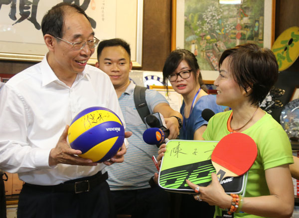You Quan (left), top leader of Fujian province, gives a volleyball signed by Chen Zhonghe, former head coach of China women's volleyball team, and a table-tennis paddle to a resident of Taipei's Zhongshun neighborhood during a visit on Thursday. Hu Meidong / China Daily