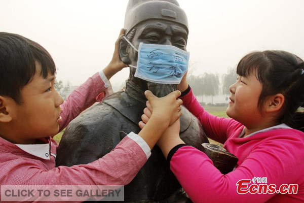 Children put mask on a sculpture to 'protect' it from smog during an environmental awareness campaign at their school in Guangping county, North China's Hebei province on Friday, October 10, 2014. [Photo: China News Service/ Cheng Xuehu]