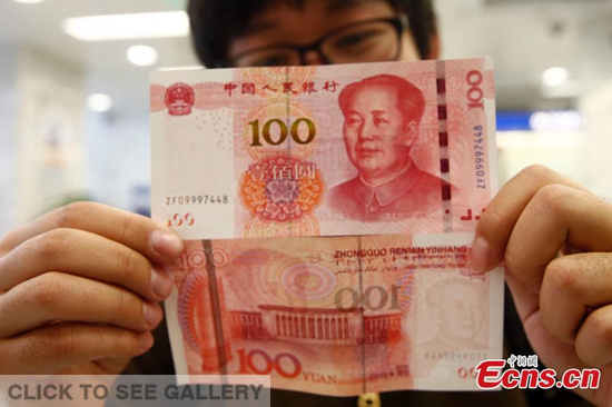 A resident shows new 100-yuan bank notes in a branch of the Bank of Communications in Beijing on November 12, 2015. The new 100-yuan bank note is put into use from Thursday, November 12. (Photo: China News service/ Zhang Hao)