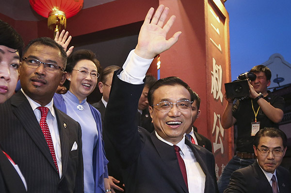 Premier Li Keqiang and his wife Cheng Hong greet the public in front of a store selling specialized products during the couple's visit to Malacca on Sunday. (Photo/Xinhua)