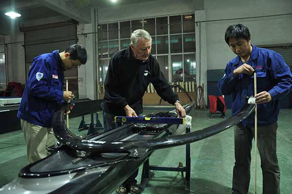 Klaus Filter instructs Chinese workers at Sino Eagle Group, a leading manufacturer of rowing shells in Fuyang, Zhejiang province. The German designer is a witness-and a major contributor-to the company's growth over the past two decades.(Photo: China Daily/Liu Xiangrui)