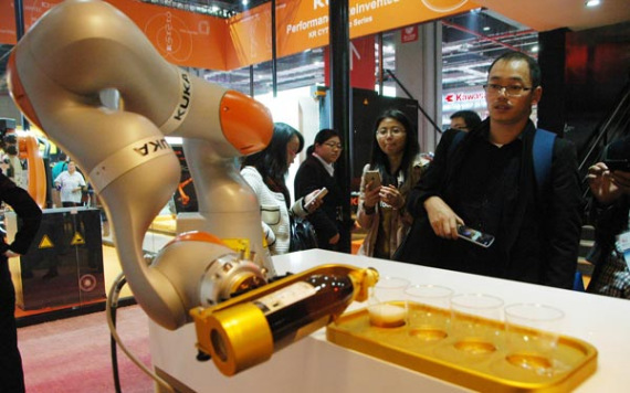 Kuka robot pours wine at a fair in Shanghai in November 2015. (Photo/China Daily)