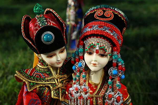 Buteelchi dolls, made by Mongolian designer Baatar and his team, are displayed on the grassland. (Photo/China Daily)