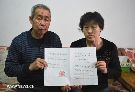 Li Sanren (L) and Shang Aiyun, parents of Huugjilt, who was wrongly executed for rape and murder at age 18, show the verdict of state compensation totaling more than 2 million yuan (about $322,000) in Hohhot, capital of north China's Inner Mongolia Autonomous Region, on Dec 31, 2014. On Dec 15, 2014. (Photo/Xinhua)