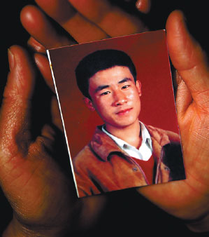 Hugjiltu's mother, Shang Aiyun, holds a photo of her son, who was wrongfully executed 18 years ago. (Photo by Guo Tieliu/for China Daily)