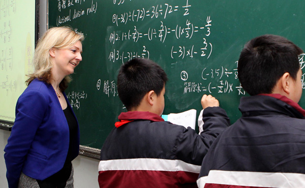 Elizabeth Truss, then British parliamentary undersecretary of state for education and childcare, looks on as two students demonstrate math skills in a primary school in Shanghai during an exchange program in 2014. (Photo/Xinhua)