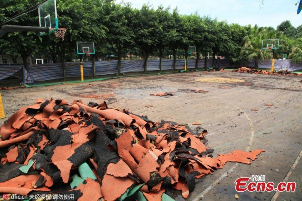A bulldozer demolishes synthetic running tracks and sports fields at a private elementary school in Chengdu City, the capital of Southwest China's Sichuan Province, June 15, 2016.