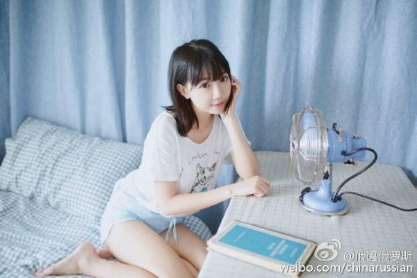 The Chinese woman poses against a baby blue background with the blue manual. (Photo from Sina Weibo)