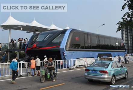 The transit elevated bus TEB-1 is on road test in Qinhuangdao, north China's Hebei Province, Aug. 2, 2016. China's home-made transit elevated bus, TEB-1, conducted a road test running Tuesday. The 22-meter-long, 7.8-meter-wide and 4.8-meter-high TEB-1 can carry up to 300 passengers. The passenger compartment of this futuristic public bus rises far above other vehicles on the road, allowing cars to pass underneath. (Xinhua/Luo Xiaoguang)