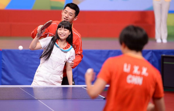 Zhang Jike, men's table tennis singles silver medalist in Rio Olympics, teaches a fan playing against Li Xiaoxia, a key member of Chinese women's team, at the Queen Elizabeth Stadium in Hong Kong, Aug 28, 2016. (Photo/Xinhua)