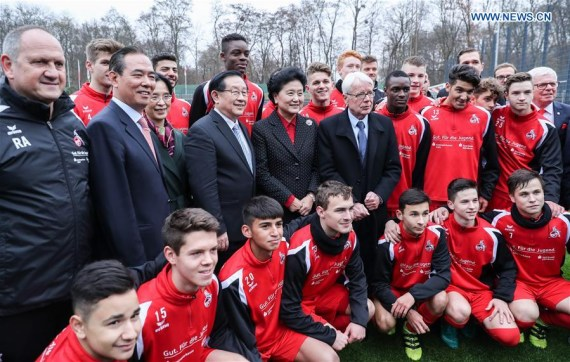 Chinese Vice Premier Liu Yandong (5th L, 2nd Row) poses with youth players from FC Cologne after the first China-Germany Football Development Symposium at the German Bundesliga football club FC Cologne in Cologne, Germany, Nov. 26, 2016.