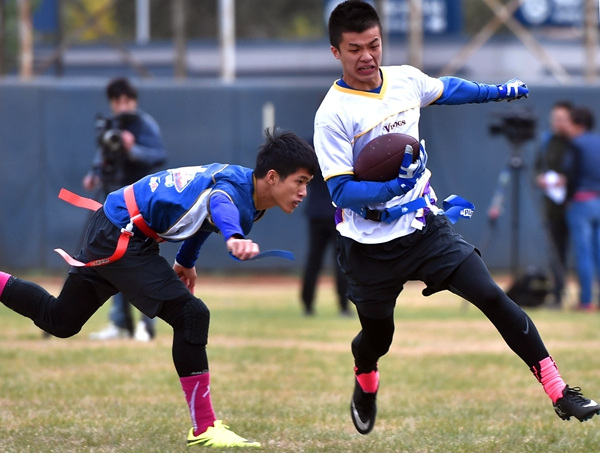 A Guangzhou University of Chinese Medicine player pulls the flag belt off the waist of his opponent at the final of the eighth NFL China University Bowl in Beijing on Oct 30.Nfl China / For China Daily