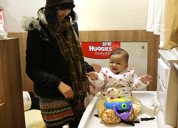A mother tends to her baby in a nursing room at a shopping mall in Shanghai. YANG SHICHAO/XINHUA