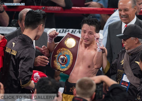 Zou Shiming (C) of China celebrates after defeating Prasitak Phaprom of Thailand in a WBO flyweight title boxing match in Las Vegas, the United States, Nov. 5, 2016. (Photo/Xinhua)
