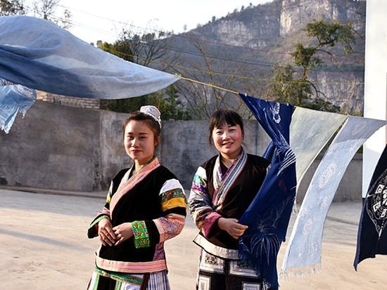 Photo taken on Feb 21 shows Cai Qun(R) in Miao costumes. (Photo/Xinhua)