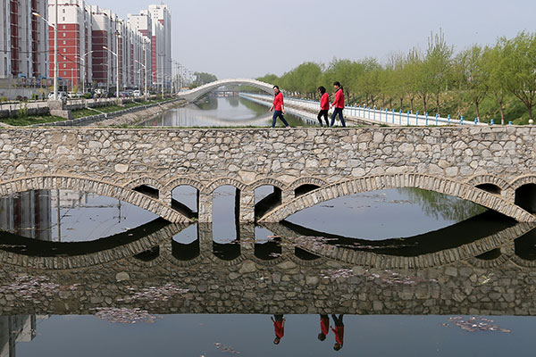 Residents walk across a bridge near a residential area in Anxin county in Xiongan New Area on Wednesday. All housing sales in the new area have been banned.Wang Zhuangfei / China Daily