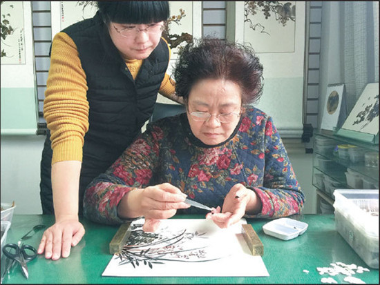Xu Nannan and her daughter create feather artwork at their studio in Chongqing.