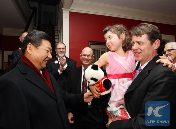 Photo taken on Feb. 15, 2012 shows Xi Jinping (L), then Chinese Vice President, presents the granddaughter of his old friend Sarah Lande with a panda doll in Muscatine, Iowa, the United States. (Xinhua/Lan Hongguang)