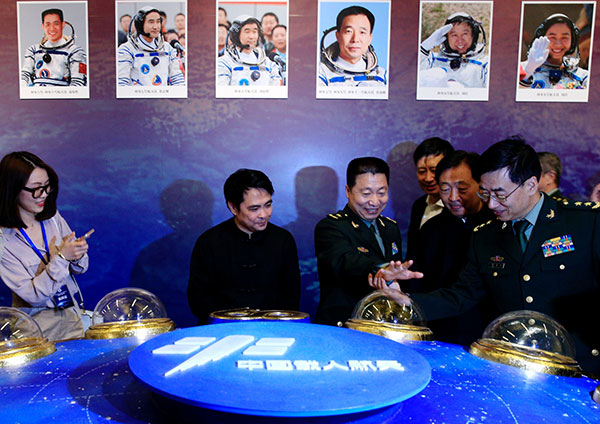 China's first man in space, Yang Liwei, compares his hand with his preserved print displayed at an exhibit about China Space Day at the National Museum of China in Beijing. JIANG DONG/CHINA DAILY