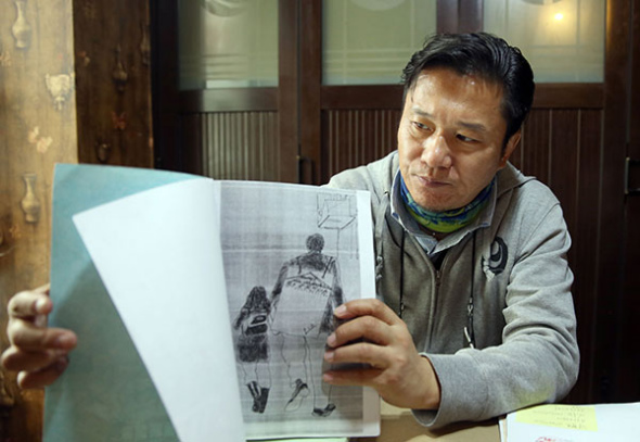 Guo Li, who was recently exonerated of blackmail after serving five years in prison, displays a drawing depicting him and his daughter. He said she was his motivation to carry on during his time in jail.(Zou Hong / China Daily)