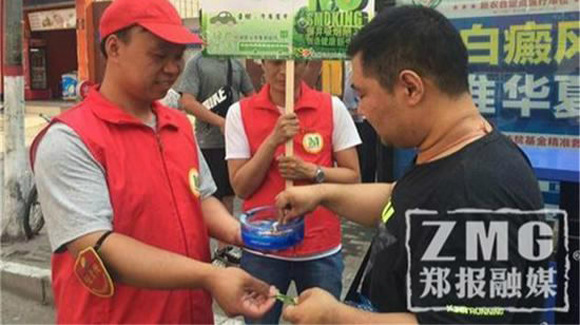 A volunteer give passenger a gum to help stop smoking. (Photo//Zhengzhou Evening Newspaper)