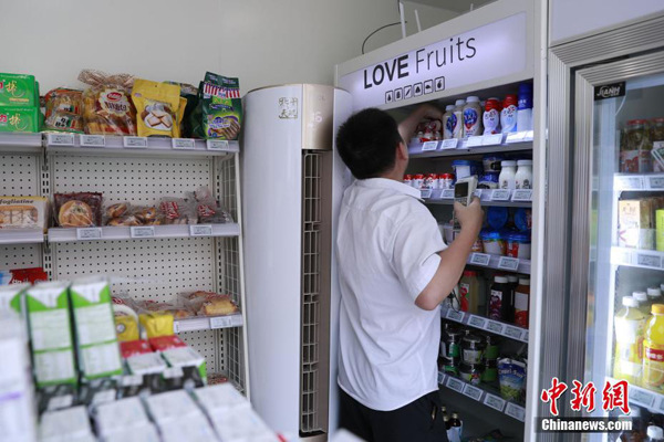 An employee stocks a refrigerator in the unmanned convenience store on Wednesday. (Photo/Chinanews.com)