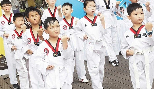 Children practice taekwondo yesterday in Yangpu District to mark China's National Fitness Day. Shanghai is making the building of sports facilities a priority and more venues as well as more jogging paths were announced yesterday. (Xinhua)