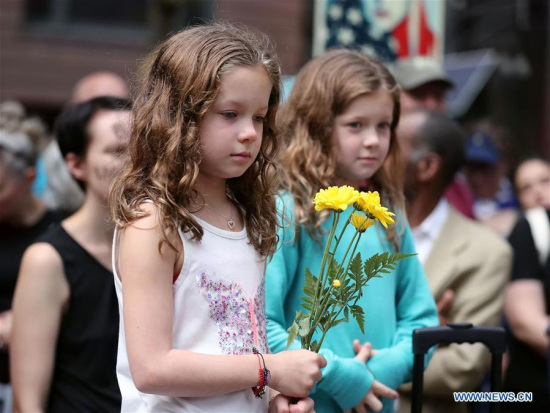 A girl holding a bunch of flowers participates in an evening vigil at Federal Plaza in Chicago, the United States, on Aug. 13, 2017. (Xinhua/Wang Ping)