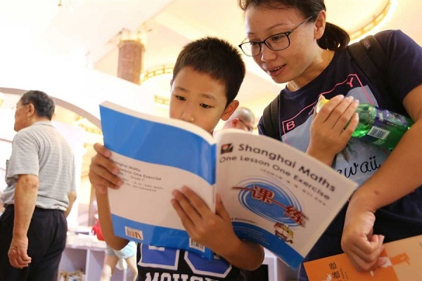 """A boy reads attentively the English version of """"One Lesson One Exercise"""" at Shanghai Book Fair where the math textbooks enjoy great popularity. (Wang Ronjiang)"""