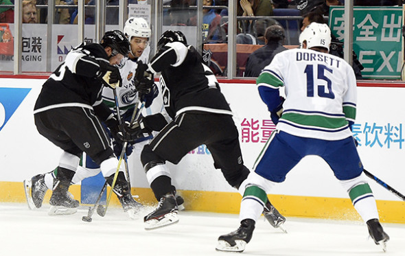 Vancouver Canucks forward Brandon Sutter battles a pair of Los Angeles Kings defenders for puck possession during Thursday's NHL China Games showdown at Mercedes-Benz Arena in Shanghai. The Kings won 5-2, with a rematch set for Saturday afternoon at Wukesong Arena in Beijing. (Photo/China Daily)