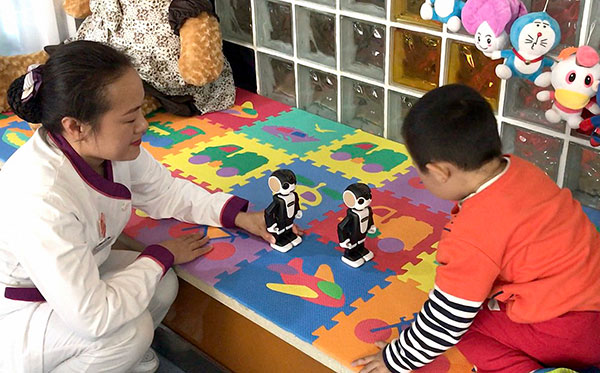 A child with autism interacts with robots at Harbin Children's Hospital, as part of an innovative approach to treatment. (Zhou Huiying/China Daily)