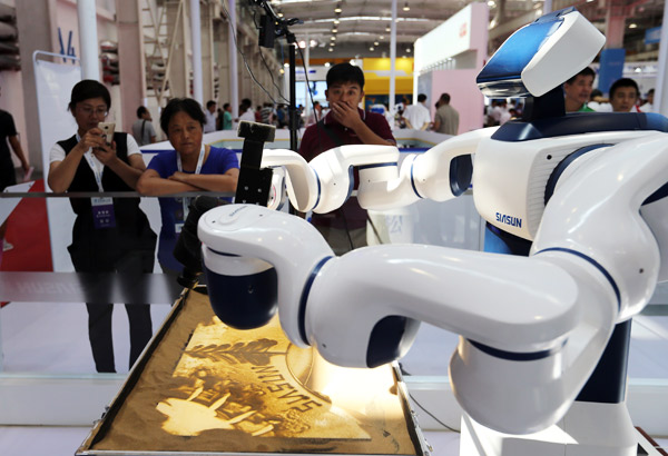 An AI robot shows its skills as per technicians' instructions at the 2017 World Robot Conference in Beijing in August. (Photo by Wang Zhuangfei/For China Daily)