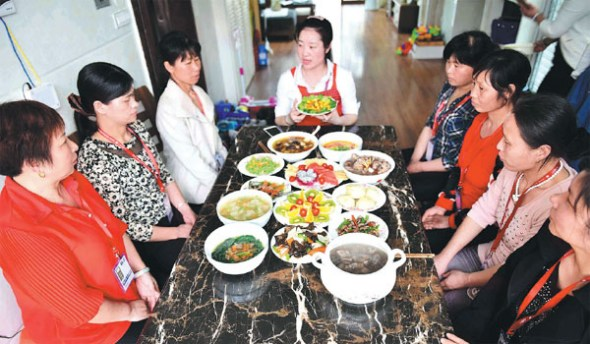Maternity nurses attend a training session in Ji'an, Jiangxi province, in May last year, on how to cook nutritious meals for women who just give birth to a baby. (Li Fusun / For China Daily)