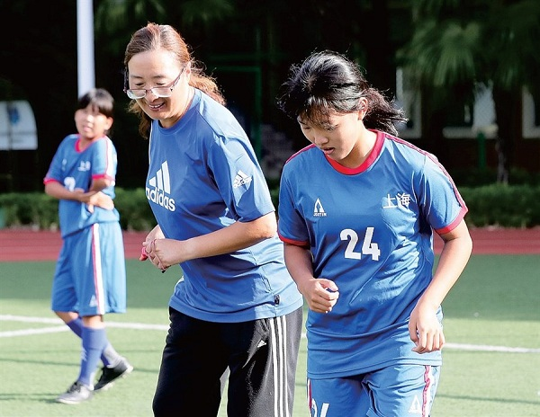 Qian Hui (middle), who is also known as the godmother of women's football in China, trains with the players.