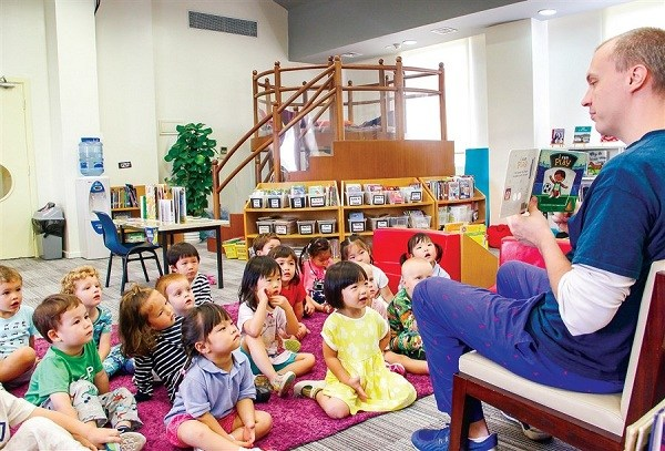 "Joshua Ballim, librarian at SCIS Hongqiao ECE campus, reads the book to the students on International Literacy Day with the theme of ""Cozy up with a good book."""