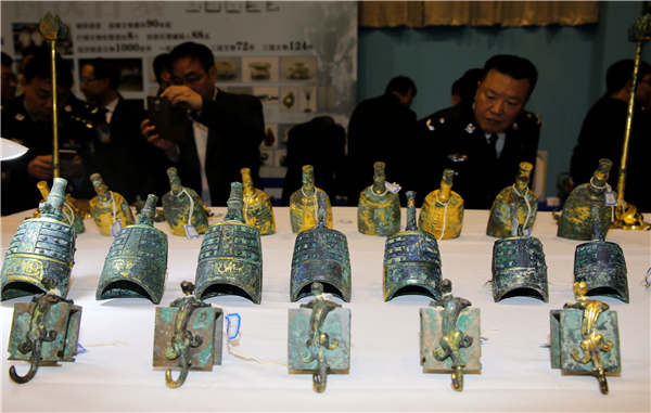 People examine relics on Tuesday that were recovered in a special operation in Xi'an, Shaanxi province. The launch of China's national internet platform that provides information about lost or stolen cultural relics will help netizens create even more successes. (Photo by Huo Yan/China Daily)